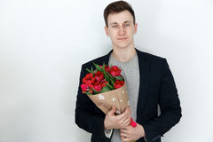 Young man with tulip bouquet, white background Stock Image