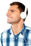 Young man tuned into music. Cheerful young man with headphones listening to music looking away Stock Photography