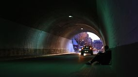 Young man in a tunnel looking cars stock video footage