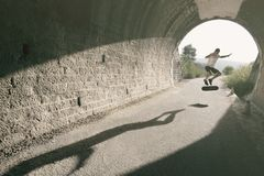 Young man in tunnel with skateboard stock image