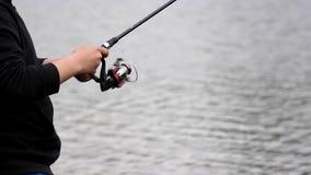 Young man turning a fishing reel near lake stock video