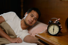 Young man turning off the alarm clock stock image