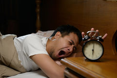 Young man turning off the alarm clock royalty free stock images