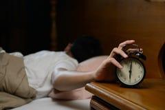 Young man turning off the alarm clock stock photos