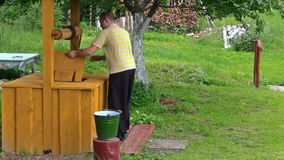 Young man turning old rural yellow well handle in countryside stock video footage