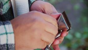 Young man turns screw on haircut machine outdoors closeup stock video footage