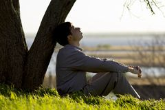 Young man turns to God with hope, the concept of faith and spirituality. Young man turns to God with questions about life sitting near a tree on the lawn, the Royalty Free Stock Photos