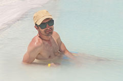 Young man in turquoise blue pool on sunny day Royalty Free Stock Image