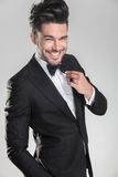 Young man in tuxedo ajusting his bow tie Stock Images