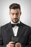 Young man in tuxedo with bow tie holding mobile phone texting message Stock Photography