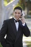 Young Man In Tuxedo Using Cell Phone at Quinceanera Stock Image