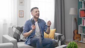 Young man with tv remote playing on invisible air drums.  stock video footage
