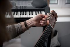 Young man twisting guitar pads for adjusting strings royalty free stock images