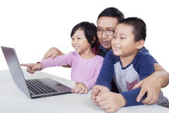 Young man and two children using laptop. Picture of a young male teacher and two cheerful children using laptop together on the table, isolated on white Stock Image