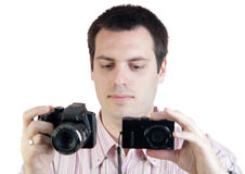 Young man with two digital cameras Royalty Free Stock Photography