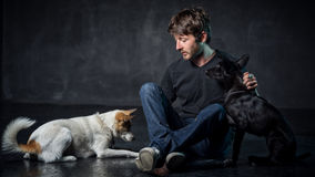 Young man and two dogs Stock Photos