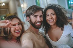 Young man and two funny girls posing in front of camera