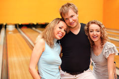 Young man and two girls embrace in bowling club. Young men and two happy beautiful girls embrace in bowling club Royalty Free Stock Photos