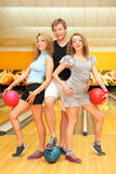 Young man and two girls hold balls in bowling club Royalty Free Stock Photo