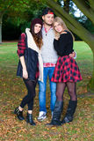 A young man with two girls in a park. Stock Photos