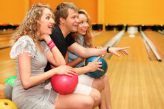 Young man and two girls sit, hold balls in bowling Royalty Free Stock Image