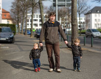 Young man and two little boys walking through spring city Stock Images