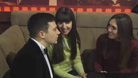 Young man and two woman talk at the club stock video