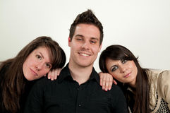 Young man with two women Stock Images