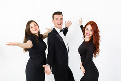 Young man and two women in black on a white background. Stock Images