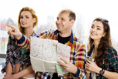 Young man and two women. Keep a map and shows the direction. Europeans. Americans. Gathered in a guided tour. Close-up Stock Photos
