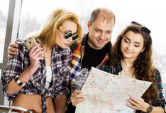 Young man and two women looking at a map. Europeans. Americans. Gathered in a guided tour. Close-up Royalty Free Stock Image