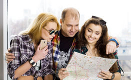 Young man and two women looking at a map. Europeans. Americans. Gathered in a guided tour. Close-up Stock Image
