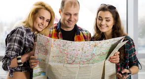 Young man and two women looking at a map. Europeans. Americans. Gathered in a guided tour. Close-up Royalty Free Stock Photo