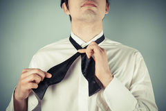 Young man tying a bow tie. Young man is showing how to tie a formal bow tie royalty free stock photo