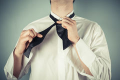 Young man tying a bow tie. Young man is showing how to tie a formal bow tie stock photography