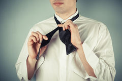 Young man tying a bow tie. Young man is showing how to tie a formal bow tie royalty free stock photography