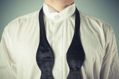 Young man tying a bow tie. Young man is showing how to tie a formal bow tie stock photo