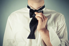 Young man tying a bow tie. Young man is showing how to tie a formal bow tie royalty free stock image