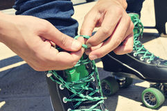 Young man tying his roller skates, with a filter effect Stock Image