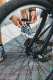 Young man tying his shoelaces before starting daily bike trips, closeup. Lifestyle Activity Footwear Concept Royalty Free Stock Images