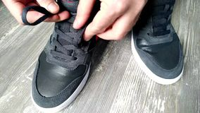 Young man tying shoelace on sport shoes indoors stock video