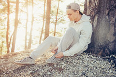 Young man tying shoelaces outdoor. Sporty young man tying shoelaces outdoor near the tree at sunny day Stock Image
