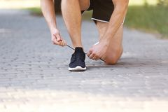 Young man tying shoelaces before running outdoors. Focus on legs Stock Photography