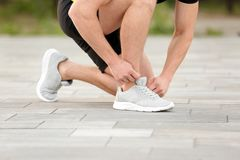 Young man tying shoelaces before running outdoors. Focus on legs Royalty Free Stock Photography