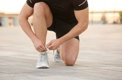 Young man tying shoelaces before running outdoors. Focus on legs Stock Photo