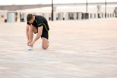 Young man tying shoelaces before running outdoors. On sunny day Royalty Free Stock Photos
