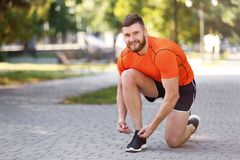 Young man tying shoelaces before running in park. On sunny day Stock Photography