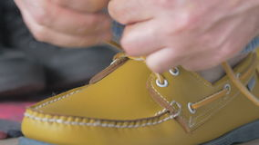 Young man tying shoelaces in shoes stock video footage
