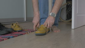 YOUNG MAN TYING SHOELACES IN SHOES stock video