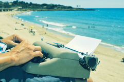 Young man typewriting on the beach. A young man typing in an old typewriter on the beach Royalty Free Stock Photography